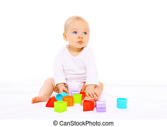 Baby playing with colorful toys on white background