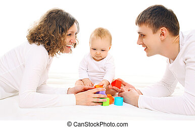 Happy family together parents and baby playing with toys