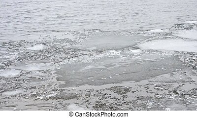 Melting floes of ice floating on water surface with waves -...