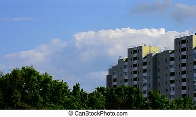 Beautiful clouds move behind modern high rise building -...