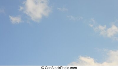 Cumulus and cirrus clouds move quickly on background of blue...