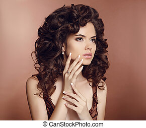 Beautiful girl with long curly hair. Makeup. Manicured nails