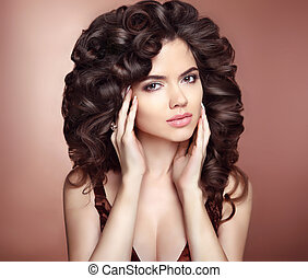 Curly hairstyle. Beautiful girl with long wavy hair