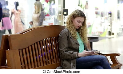 Woman typing on smartphone in shopping center