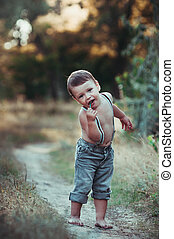 Little boy holds in his mouth lollipop on a stick outdoors...