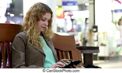 Young woman with tablet sit on bench in shopping mall