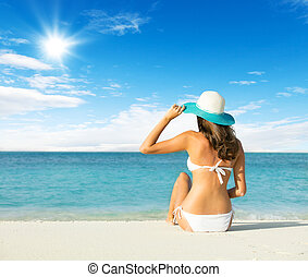 Back view of long haired young woman in swimsuit and...