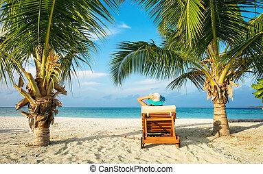 Woman relaxing on deckchair, tropical beach of Indian ocean,...