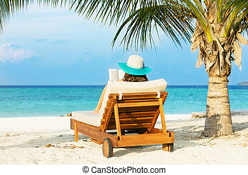 Woman relaxing and reading on deckchair, tropical beach of...
