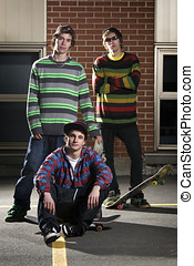 Group of three skateboarder friends