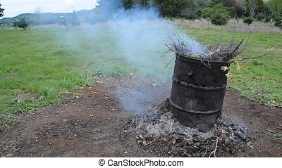 Barrel with burning sticks - An old barrel with rubbish and...