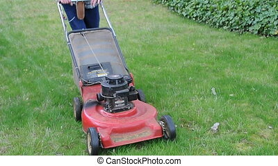 Mowing the lawn in corner - Man mows his green grass...