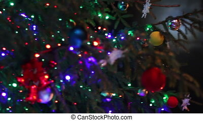 Christmas tree decorated with lights, toys at night -...