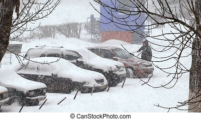 Heavy snowfall in the city snow covered cars in the parking...
