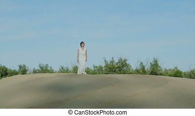 Women in white dress walking on sand dune summer - Women in...