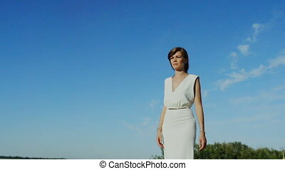 Pensive woman walking isolated blue sky - Pensive woman in...
