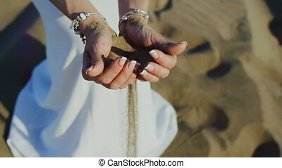 Woman with sand falling through her hands on beach
