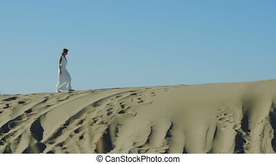 Woman in white dress walks on sand dune - Woman in white...