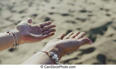 The woman rotates their hands with sand