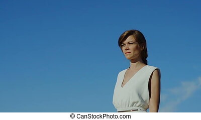 Pensive woman in dress walking isolated blue sky - Pensive...