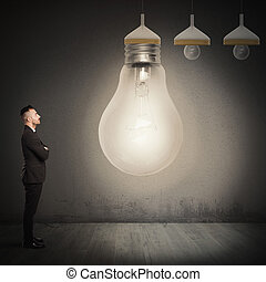 Big idea - Businessman looks at a big light bulb
