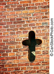 Cross in old brick wall