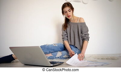 Young pretty student sitting on the floor use her laptop to...