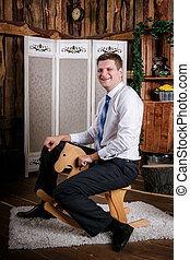 Happy childish young man is riding on the wooden toy horse. Adult acting like a child concept