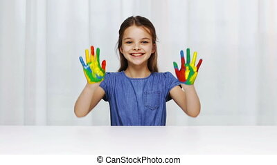 smiling girl showing painted hands