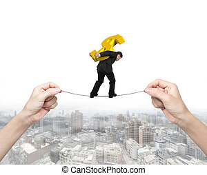 Man carrying dollar sign balancing tightrope with hands...