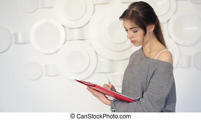 Young successful businesswoman holding red paper-folder with documents on her hands pose on camera and smile.