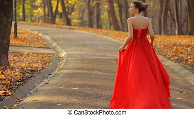 Attractive woman walking in a red long evening dress in the...