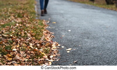 Woman walking on the sidewalk in autumn - Woman walking to...