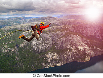 Rope jumping - Man jumping off a cliff with a rope.