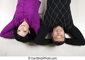 Happy couple lying down on floor - Happy young couple lying...