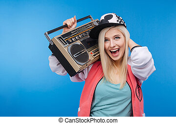 Woman holding retro boom box - Cheerful young woman holding...