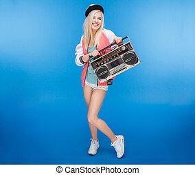 Smiling female teenager holding retro boom box - Full length...