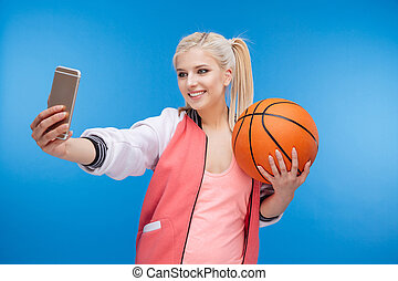 Female teenager holding basketball ball and making selfie...