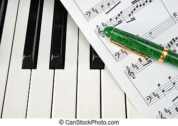 Piano keyboard with music score and pen
