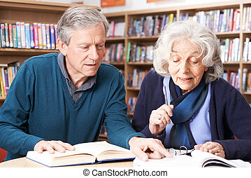 Mature Student Working With Teacher In Library