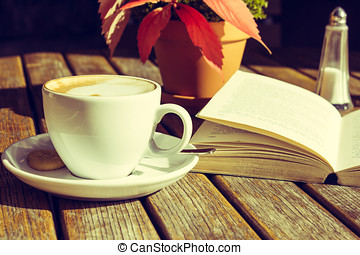 Coffee Mug and Open Book on a Wooden Table