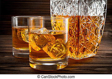 Closeup of bottle and two glasses with ice and whiskey on...