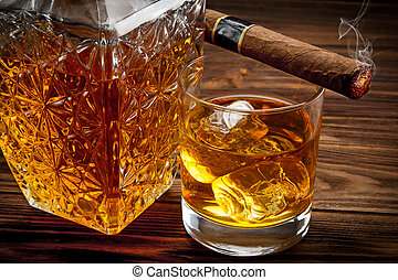 Closeup of bottle, glass with whiskey and smoking cigar on...