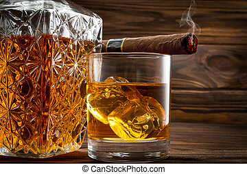 Closeup of bottle, glass with whiskey and smoldering cigar...