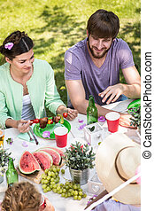 Eating at the garden party - Young woman eating skewers at...