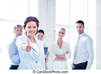 businesswoman in office showing thumbs up - business concept...
