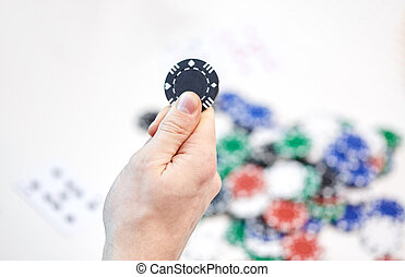 close up of male hand holding casino chip