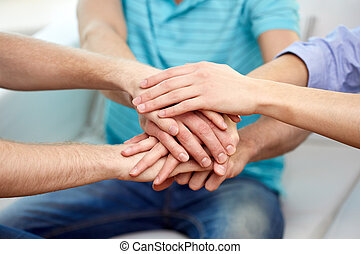 close up of friends connecting hands together - teamwork,...