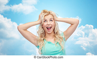 smiling young woman holding to her head or hair - emotions,...