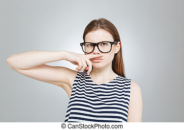 Funny teenage girl in glasses making moustache with her...
